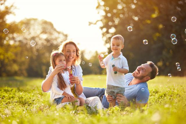 Family blowing bubbles together in a field
