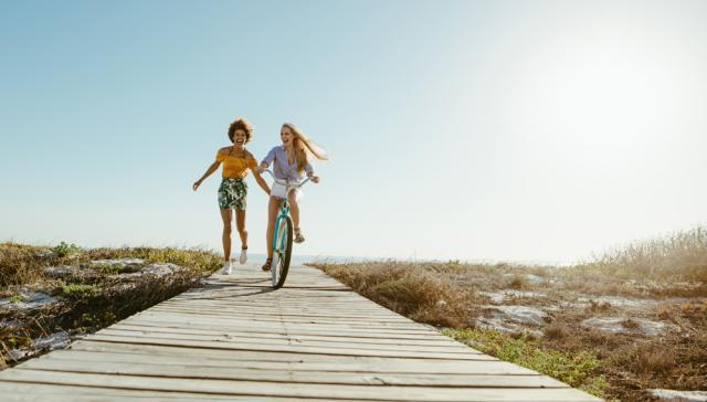 Two women, one on a bike, going down a boardwalk