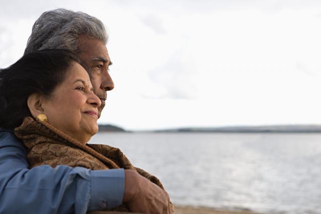 Elderly couple cuddling on a beach