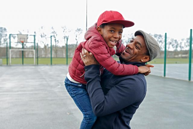 Man hold his smiling son on a basketball court