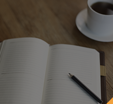 Notebook laying open on a desk with a cup of coffee