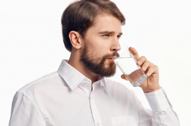 A man drinking a glass of water
