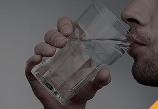 Un homme buvant de l'eau pour éviter de fumer.