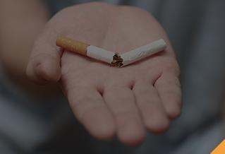an open palm holding a broken cigarette.
